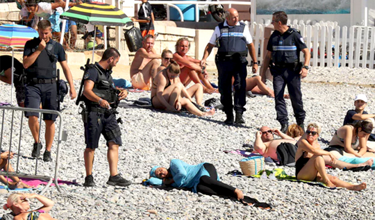 French police force Muslim woman to remove burkini top at beach